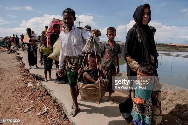 COX'S BAZAR BANGLADESH SEPTEMBER 13 Saiful Rahman 30 walks towards Teknaf mainland with his family after crossing the Naf river from Myanmar