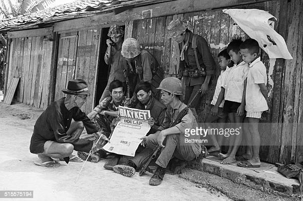 Government troops and villagers read a newspaper with headline reporting ceasefire signed in Paris June 14 a moment before the new ceasefire...