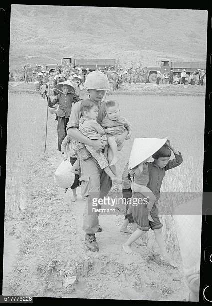 A Korean soldier caries a couple of Vietnamese tots across a rice paddy field recently He was helping in the evacuation of 600 refugees from Mong...