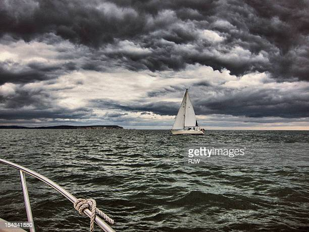 sail boat on storm sea and storm clouds - overcast stock pictures, royalty-free photos & images