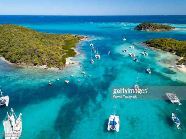 sail boats and catamarans moored near uninhabited islands of tabago cays, grenadines, 2019 - west indies stock pictures, royalty-free photos & images