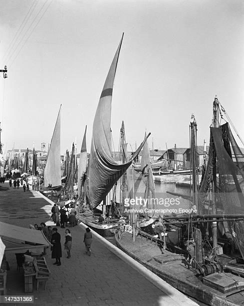 Sail boats docking beside the market Chioggia Venice 1950