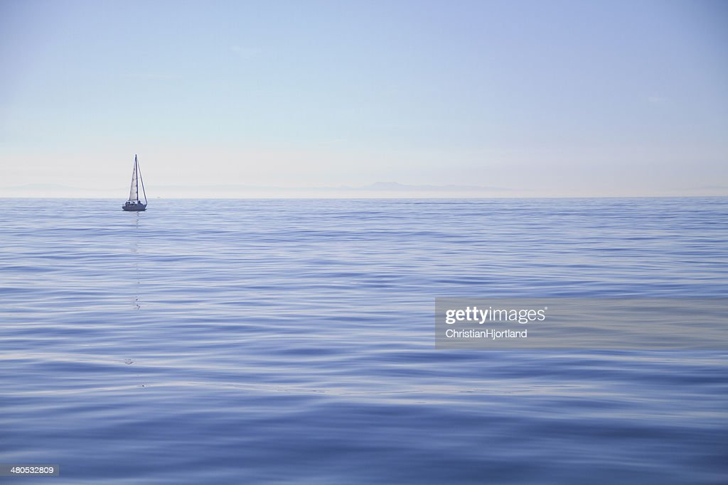 Sailboat alone on the ocean : Stock Photo