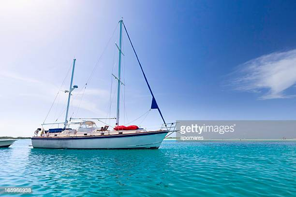 Sailboat anchored at a tropical turquoise island