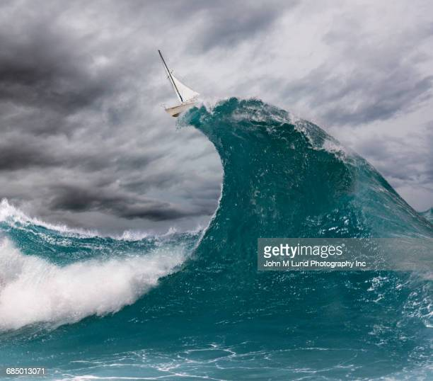 Sailboat balancing on top of enormous wave in ocean