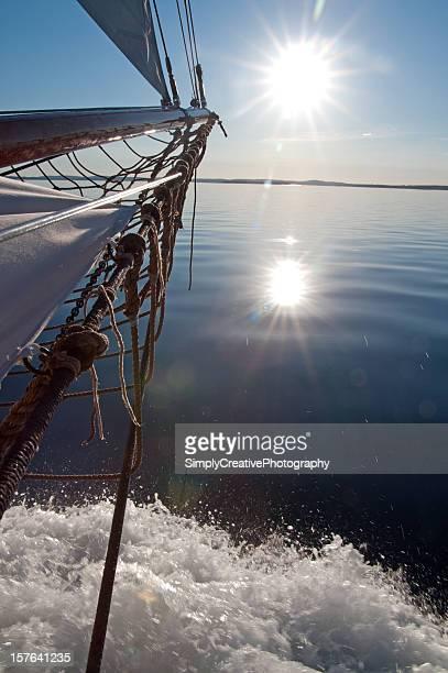 segelschiff schleife auf dem wasser bei sonnenuntergang - schiffsbug stock-fotos und bilder