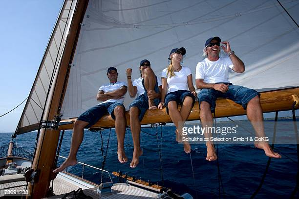 sailboat captain and crew sitting side by side on boom, laughing - sail boom stock pictures, royalty-free photos & images