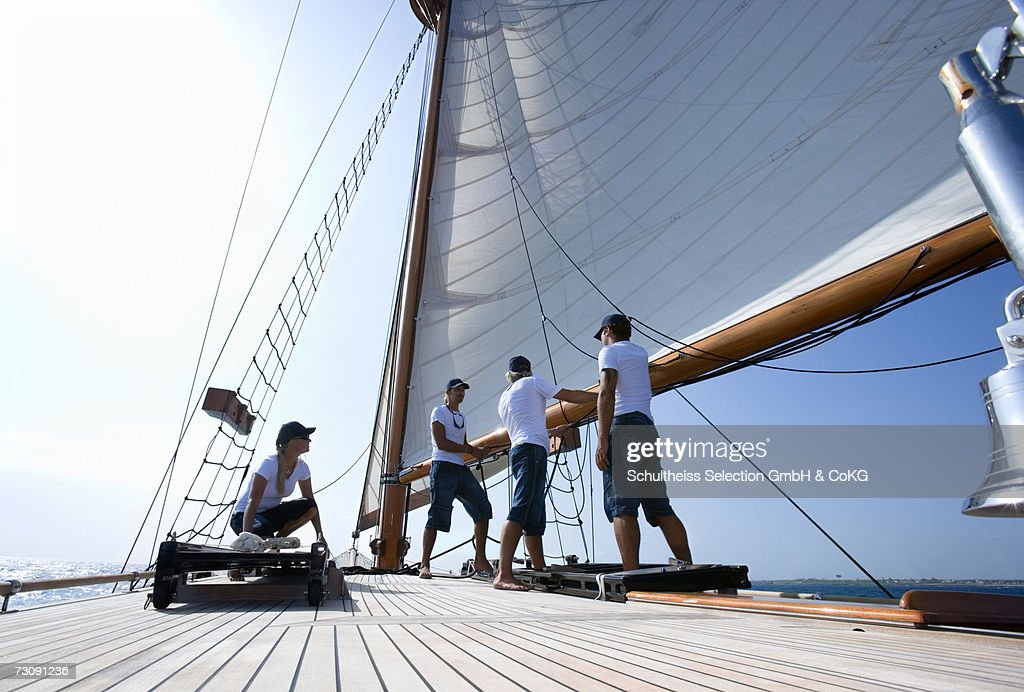 Sailboat captain and crew working on deck, ground view : Stock Photo