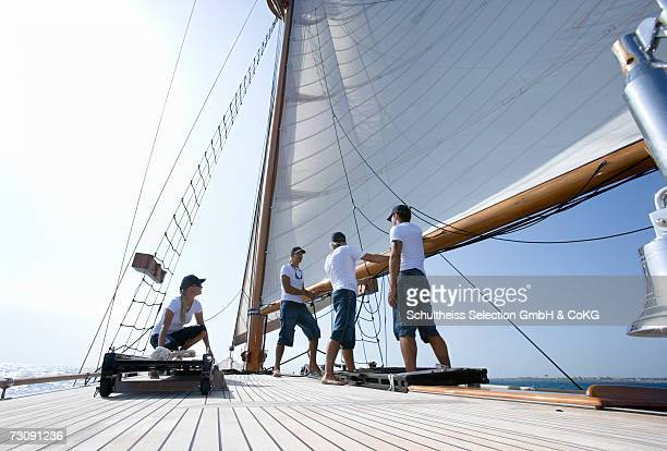 Sailboat captain and crew working on deck, ground view