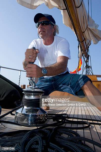 Sailboat captain on deck winding rope with capstan