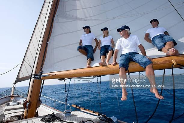 sailboat captain sitting on boom with crew standing behind him - tuig mast stockfoto's en -beelden