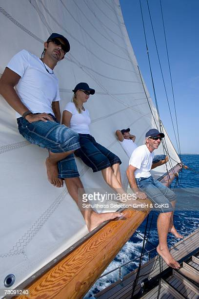sailboat captain sitting on boom with crew standing behind him - sail boom stock pictures, royalty-free photos & images