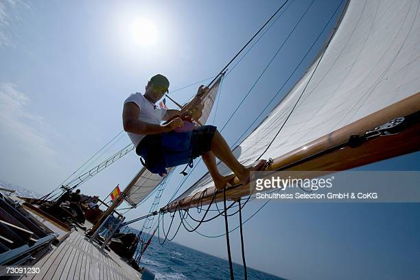 Sailboat crewman suspended from mast with feet braced against boom