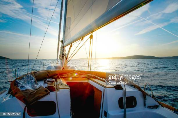 sailboat crossing at dusk - high society stock pictures, royalty-free photos & images