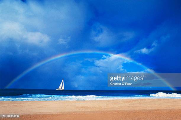 Sailboat Cruising Under Rainbow