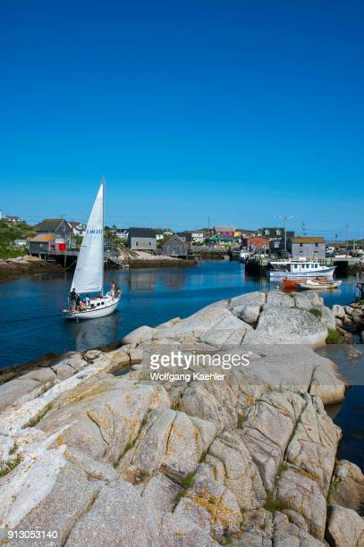 Sailboat entering the natural harbor of the fishing village of Peggy's Cove near Halifax Nova Scotia Canada