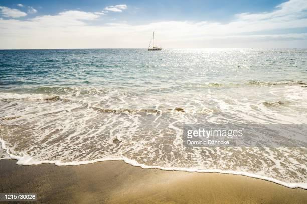 """sailboat in """"bahía del duque"""" beach, south of tenerife island - dähncke fotografías e imágenes de stock"""