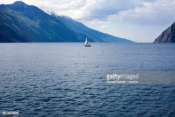 Sailboat In Lake Garda With Mountains Against Sky