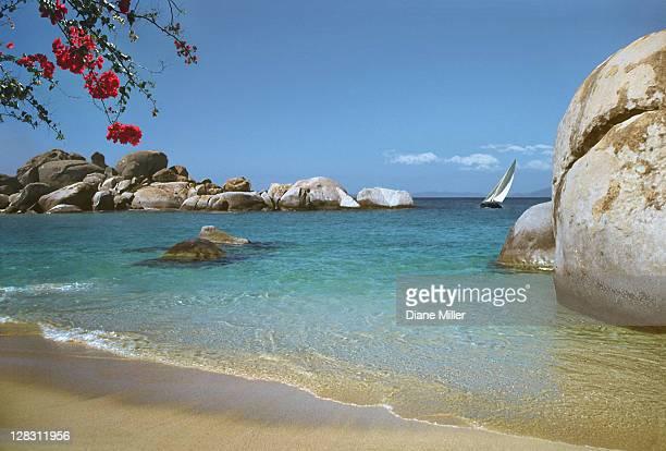 sailboat in ocean near boulders along beach, the baths, virgin gorda, british virgin islands - islas de virgin gorda fotografías e imágenes de stock