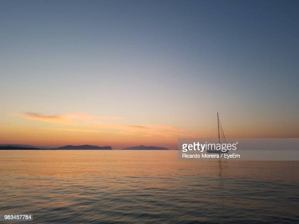 sailboat in sea against sky during sunset - spetses stock pictures, royalty-free photos & images