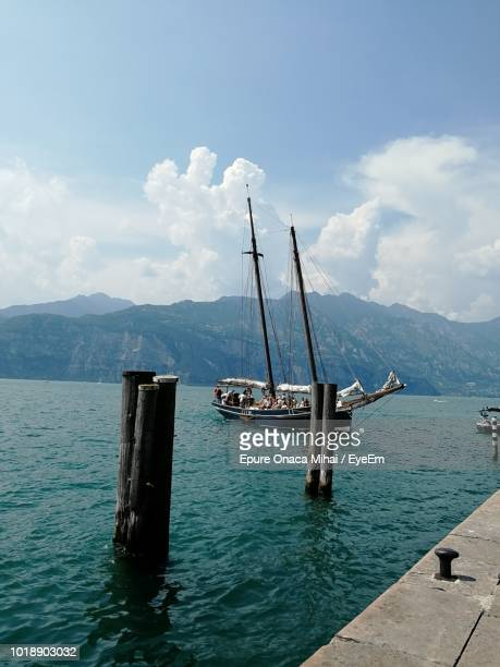 sailboat in sea against sky - malcesine stock pictures, royalty-free photos & images
