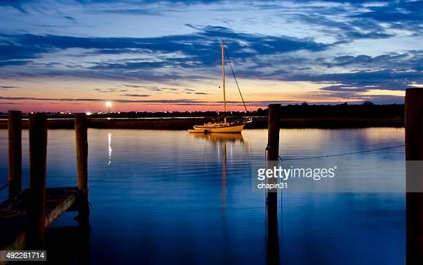 Barca a vela in acqua scintillante al crepuscolo