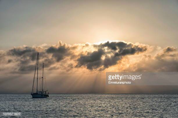 Sailboat in the Aegean sea with a cloudy sky at sunset.