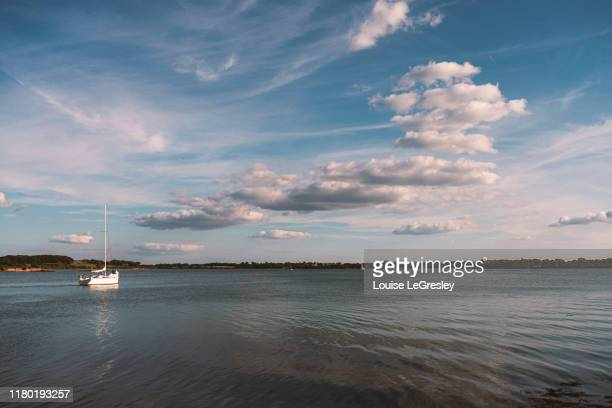 sailboat in the distance on a beautiful sunny day - ヴァンヌ ストックフォトと画像