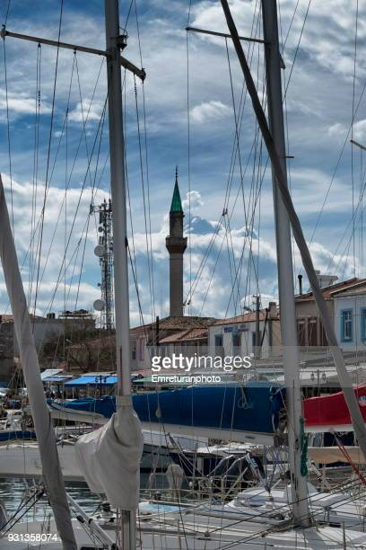 sailboat masts and minaret of urla mosque . - emreturanphoto stock pictures, royalty-free photos & images
