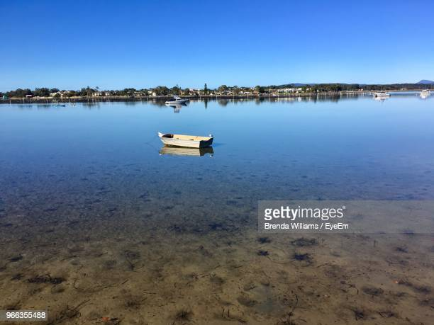 sailboat moored on sea against clear sky - merimbula stock pictures, royalty-free photos & images