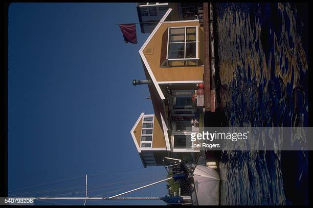 A sailboat moors beside a typical Seattle houseboat on Lake Union in the center of the city Washington USA