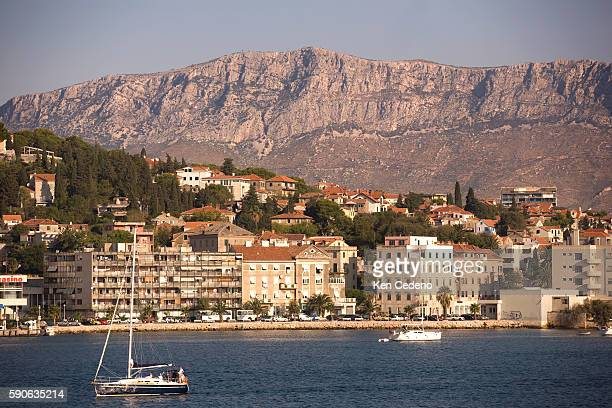 A sailboat moves from the harbor area of Hvar with a mountain ridge overlooking the town in the background | Location Hvar Croatia