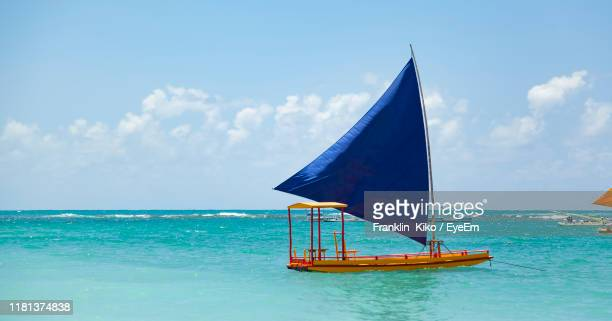 sailboat on sea against sky - porto galinhas stock photos and pictures