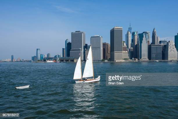 A sailboat on the East River in front of the New York Skyline