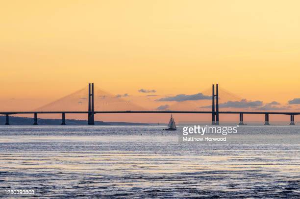 Sailboat passes alongside the Prince of Wales Bridge which links England and Wales via the M4 and is formerly known as the Second Severn Crossing, at...