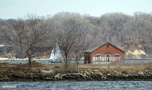 A sailboat passes behind an abandoned building on Hart Island on April 5 2014 in New York Each white plastic pipe near the building marks an infant...