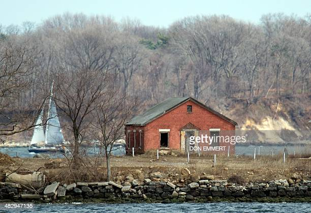 Sailboat passes behind an abandoned building on Hart Island on April 5, 2014 in New York. Each white plastic pipe near the building marks an infant...