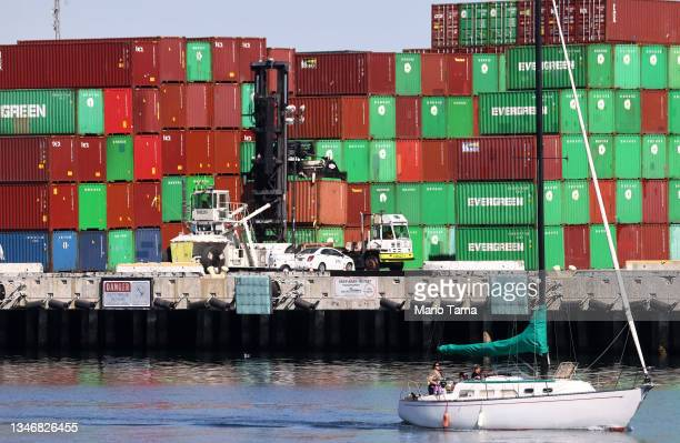 Sailboat passes cargo containers stacked at the Port of Los Angeles, the nation's busiest container port, on October 15, 2021 in San Pedro,...