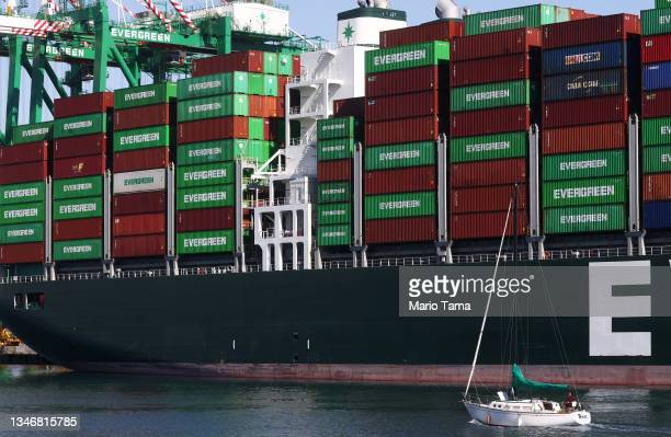 Sailboat passes cargo containers stacked on a container ship at the Port of Los Angeles, the nation's busiest container port, on October 15, 2021 in...
