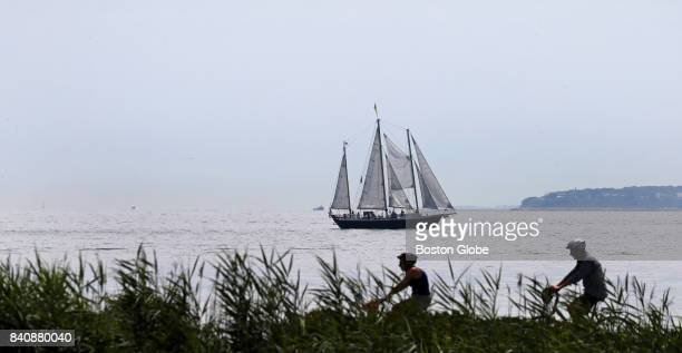 A sailboat passes through the water off Cape Cod as cyclists ride along a bike path in Falmouth MA on Aug 15 2017
