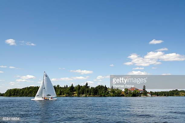 sailboat sailing by the royal lake of the woods yacht club - kenora stock pictures, royalty-free photos & images