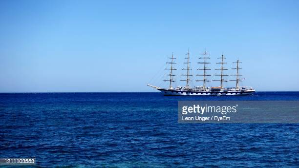 sailboat sailing in sea against clear blue sky - giardini naxos stock pictures, royalty-free photos & images