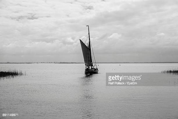 sailboat sailing in sea against cloudy sky - voilier noir et blanc photos et images de collection