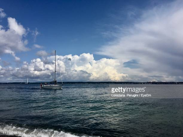 sailboat sailing in sea against sky - loredana perugini stock pictures, royalty-free photos & images