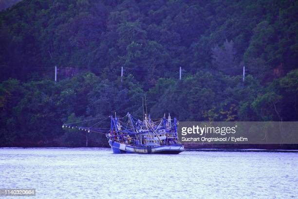 sailboat sailing in sea against trees - chanthaburi stock pictures, royalty-free photos & images