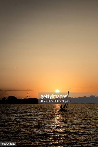 sailboat sailing in sea at sunset - albrecht schlotter stock photos and pictures