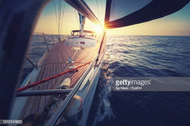 sailboat sailing in sea during sunset - sailor stock pictures, royalty-free photos & images