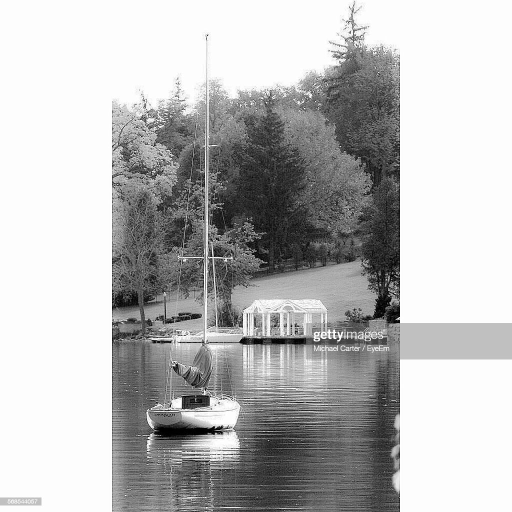 Sailboat Sailing On River Against Trees On Field : Stock Photo