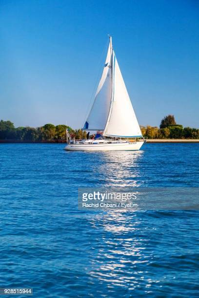 sailboat sailing on sea against clear blue sky - small boat stock pictures, royalty-free photos & images