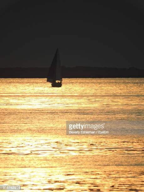 Sailboat Sailing On Sea Against Clear Sky At Sunset